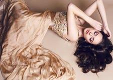 Όμορφο κορίτσι με την πολυτελή σκοτεινή τρίχα στην τοποθέτηση φορεμάτων τσεκιών στο στούντιο Στοκ Φωτογραφία
