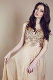 Όμορφο κορίτσι με την πολυτελή σκοτεινή τρίχα στην τοποθέτηση φορεμάτων τσεκιών στο στούντιο Στοκ Εικόνες