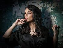 Όμορφο κορίτσι με την τοποθέτηση makeup ενάντια στον παλαιό τοίχο με το πράσινο χρώμα αποφλοίωσης Όμορφο brunette στο Μαύρο Ελκυσ Στοκ Εικόνες