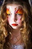 Όμορφο κορίτσι με τη ζωγραφική προσώπου στο μαύρο υπόβαθρο Στοκ Εικόνες
