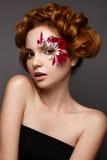 Όμορφο κορίτσι με τη δημιουργική σύνθεση με τα floral appliques Το πρότυπο στο ύφος ρομαντικού με τα πέταλα λουλουδιών γύρω από τ στοκ εικόνα με δικαίωμα ελεύθερης χρήσης