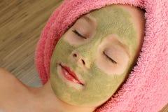 Όμορφο κορίτσι με τη μάσκα αργίλου του προσώπου Στοκ Εικόνες