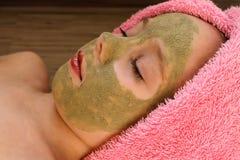 Όμορφο κορίτσι με τη μάσκα αργίλου του προσώπου Στοκ φωτογραφία με δικαίωμα ελεύθερης χρήσης