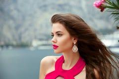 Όμορφο κορίτσι με τη μακριά κυματιστή τρίχα, τα κόκκινα χείλια και το σκουλαρίκι μόδας στοκ εικόνα