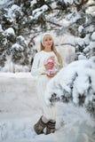 Όμορφο κορίτσι με τη μακριά σγουρή τρίχα και τα άσπρα ενδύματα που έχουν τη διασκέδαση Στοκ Φωτογραφίες