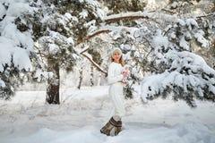 Όμορφο κορίτσι με τη μακριά σγουρή τρίχα και τα άσπρα ενδύματα που έχουν τη διασκέδαση Στοκ Εικόνα