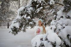 Όμορφο κορίτσι με τη μακριά σγουρή τρίχα και τα άσπρα ενδύματα που έχουν τη διασκέδαση Στοκ εικόνα με δικαίωμα ελεύθερης χρήσης