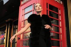 Όμορφο κορίτσι με τη σκοτεινή τρίχα που περπατά από την οδό, κόκκινο τηλέφωνο β Στοκ Φωτογραφίες