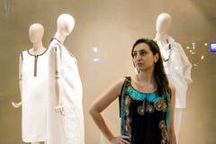 Όμορφο κορίτσι με τη σκοτεινή τρίχα που στέκεται μπροστά από ένα κατάστημα πολυτέλειας Στοκ Φωτογραφία