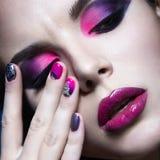 Όμορφο κορίτσι με τη φωτεινή δημιουργική μόδα makeup και τη ζωηρόχρωμη στιλβωτική ουσία καρφιών Σχέδιο ομορφιάς τέχνης Στοκ Φωτογραφία