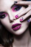 Όμορφο κορίτσι με τη φωτεινή δημιουργική μόδα makeup και τη ζωηρόχρωμη στιλβωτική ουσία καρφιών Σχέδιο ομορφιάς τέχνης Στοκ Εικόνα