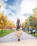 Όμορφο κορίτσι με τη χρωματισμένη τρίχα που κρατά μια βαλίτσα Στοκ Εικόνες