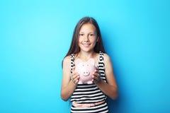 Όμορφο κορίτσι με τη piggy τράπεζα Στοκ Εικόνες