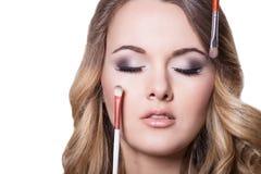 Όμορφο κορίτσι με τις βούρτσες makeup Στοκ Φωτογραφία
