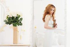 Όμορφο κορίτσι με τις καφετιές μακρυμάλλεις στάσεις κοντά σε έναν καθρέφτη που κρατά ένα λεύκωμα με τις φωτογραφίες στα χέρια της Στοκ εικόνες με δικαίωμα ελεύθερης χρήσης