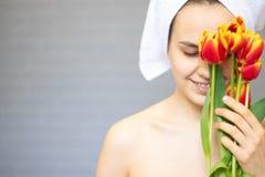 Όμορφο κορίτσι με τις τουλίπες λουλουδιών στα χέρια σε ένα ελαφρύ υπόβαθρο στοκ φωτογραφίες