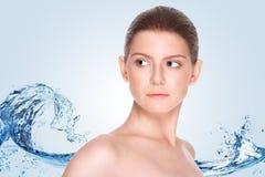 Όμορφο κορίτσι με το καθαρό δέρμα σε ένα υπόβαθρο του ραντίσματος του νερού Στοκ Φωτογραφία