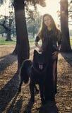 Όμορφο κορίτσι με το μεγάλο μαύρο σκυλί Στοκ Φωτογραφίες