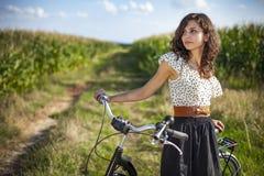 Όμορφο κορίτσι με το ποδήλατο στην πορεία στοκ εικόνες