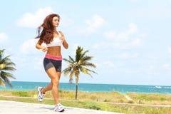 Όμορφο κορίτσι με το συμπαθητικό τρέξιμο σωμάτων κοντά στον ωκεανό Στοκ εικόνα με δικαίωμα ελεύθερης χρήσης