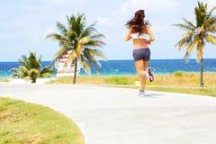 Όμορφο κορίτσι με το συμπαθητικό τρέξιμο σωμάτων κοντά στον ωκεανό Στοκ Εικόνες
