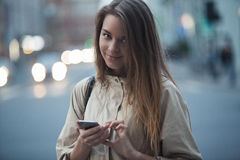 Όμορφο κορίτσι με το τηλέφωνο στην οδό στα κινούμενα αυτοκίνητα υποβάθρου Στοκ εικόνες με δικαίωμα ελεύθερης χρήσης