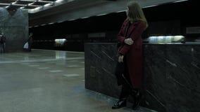 Όμορφο κορίτσι με το beanie που ακούει τη μουσική σε έναν σταθμό μετρό Γυναίκα που χρησιμοποιεί το τηλέφωνο κυττάρων της στον υπό απόθεμα βίντεο
