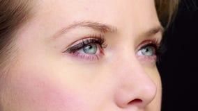 Όμορφο κορίτσι με το eyeliner που αναβοσβήνει κοντά επάνω φιλμ μικρού μήκους