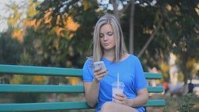 Όμορφο κορίτσι με το smartphone και το καταφερτζή απόθεμα βίντεο
