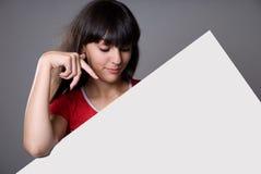 Όμορφο κορίτσι πίσω από το κενό χαρτόνι στοκ φωτογραφία με δικαίωμα ελεύθερης χρήσης