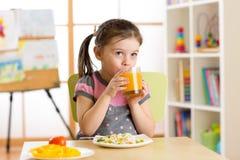 Όμορφο κορίτσι παιδιών που τρώει και που πίνει τα υγιή τρόφιμα στον παιδικό σταθμό Στοκ Εικόνες