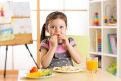 Όμορφο κορίτσι παιδιών που τρώει τα υγιή τρόφιμα στο δωμάτιο βρεφικών σταθμών Στοκ Εικόνα