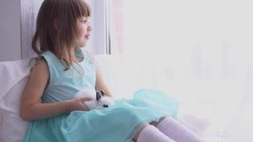 Όμορφο κορίτσι που έχει τη διασκέδαση, που αγκαλιάζει και που παίζει με το διακοσμητικό κουνέλι απόθεμα βίντεο