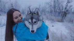 Όμορφο κορίτσι που αγκαλιάζει ένα γεροδεμένο σκυλί απόθεμα βίντεο
