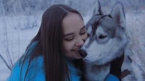 Όμορφο κορίτσι που αγκαλιάζει ένα γεροδεμένο σκυλί φιλμ μικρού μήκους