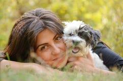 Όμορφο κορίτσι που αγκαλιάζει το σκυλί της στο δάσος φθινοπώρου Στοκ Εικόνες