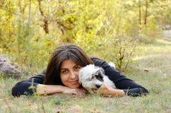 Όμορφο κορίτσι που αγκαλιάζει το σκυλί της στο δάσος φθινοπώρου Στοκ Φωτογραφίες