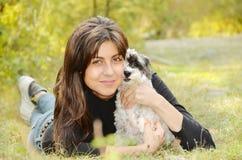 Όμορφο κορίτσι που αγκαλιάζει το σκυλί της στο βουνό Στοκ Φωτογραφία