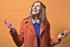 Όμορφο κορίτσι που ακούει τη μουσική με τα χέρια επάνω στοκ εικόνα