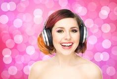 Όμορφο κορίτσι που ακούει τη μουσική σε όλα τα ακουστικά Στοκ Φωτογραφία