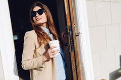 Όμορφο κορίτσι που βγαίνει από έναν καφέ και που κρατά ένα φλιτζάνι του καφέ στα γυαλιά ηλίου Στοκ Φωτογραφία