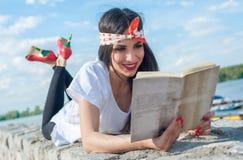 Όμορφο κορίτσι που βρίσκεται στον τοίχο και που απολαμβάνει μια ανάγνωση βιβλίων Στοκ εικόνα με δικαίωμα ελεύθερης χρήσης