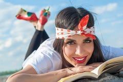 Όμορφο κορίτσι που βρίσκεται στον τοίχο και που απολαμβάνει μια ανάγνωση βιβλίων Στοκ φωτογραφίες με δικαίωμα ελεύθερης χρήσης