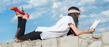 Όμορφο κορίτσι που βρίσκεται στον τοίχο και που απολαμβάνει μια ανάγνωση βιβλίων Στοκ Εικόνες