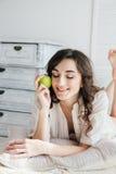 Όμορφο κορίτσι που βρίσκεται στο κρεβάτι και που κρατά τη Apple Στοκ εικόνα με δικαίωμα ελεύθερης χρήσης