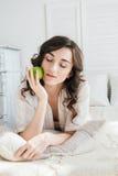 Όμορφο κορίτσι που βρίσκεται στο κρεβάτι και που κρατά τη Apple Στοκ Εικόνες