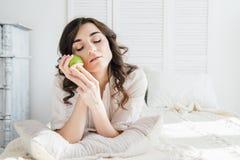 Όμορφο κορίτσι που βρίσκεται στο κρεβάτι και που κρατά τη Apple Στοκ Εικόνα