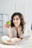Όμορφο κορίτσι που βρίσκεται στο κρεβάτι και που κρατά τη Apple Στοκ φωτογραφίες με δικαίωμα ελεύθερης χρήσης