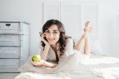Όμορφο κορίτσι που βρίσκεται στο κρεβάτι και που κρατά τη Apple Στοκ Φωτογραφία