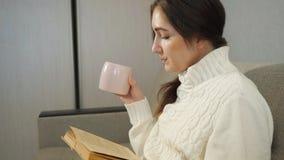 Όμορφο κορίτσι που διαβάζει ένα βιβλίο και που πίνει τον καφέ στον καναπέ στο σπίτι απόθεμα βίντεο
